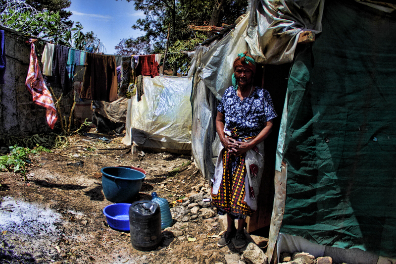 Christmas 2016 in City Cotton Nairobi. A resident standing outside her hut made from waste materials.